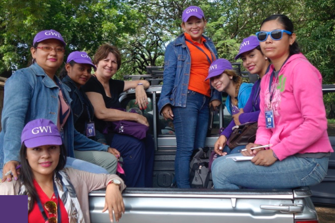 Group of Women in a bed of a truck wearing GWI hats