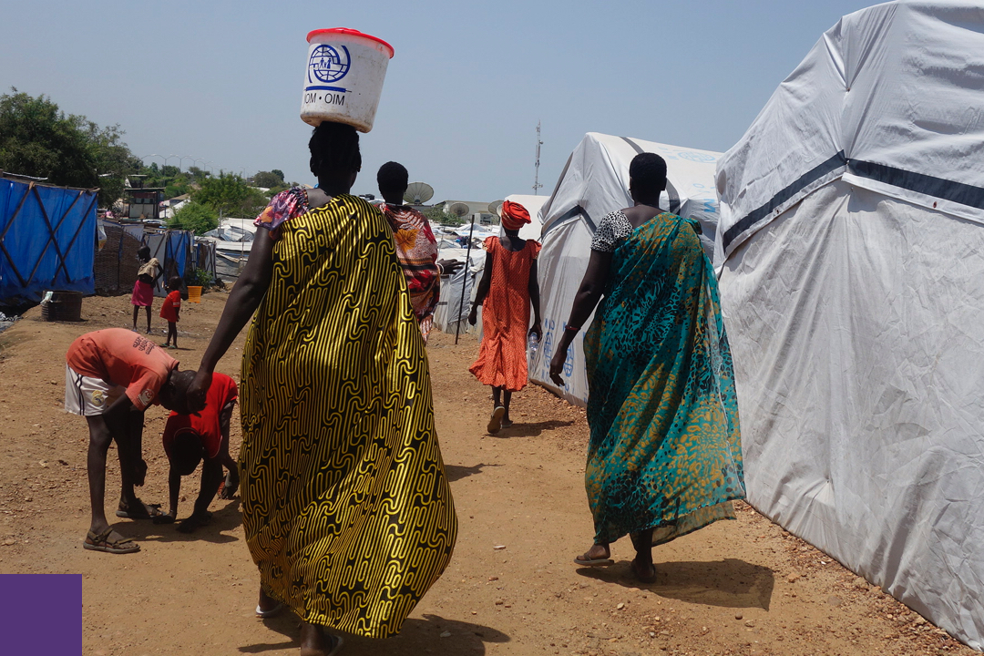 Woman with a bucket on her head walking by tents in a refugee camp